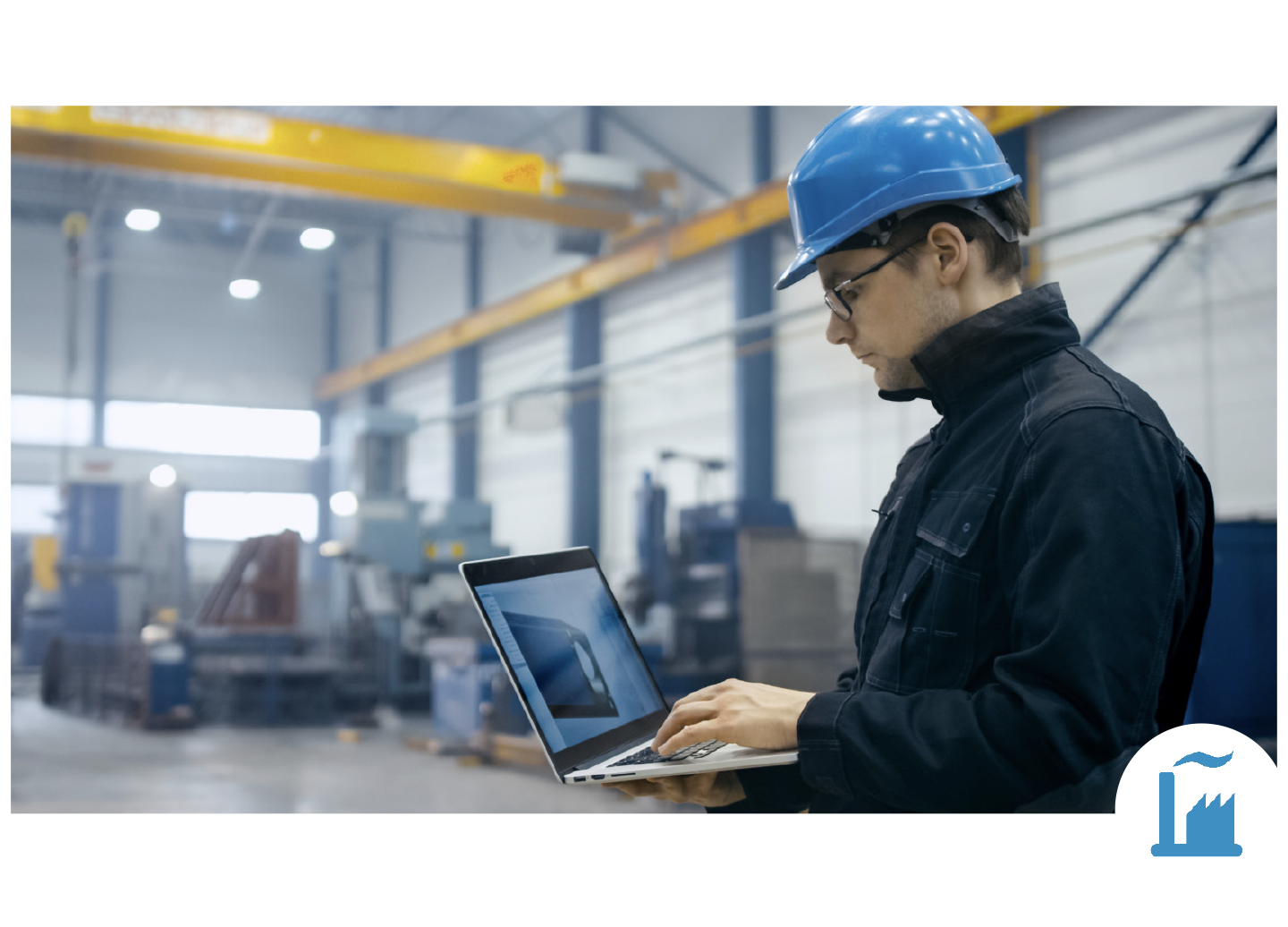 Manufacturing Worker Holding Laptop in Warehouse