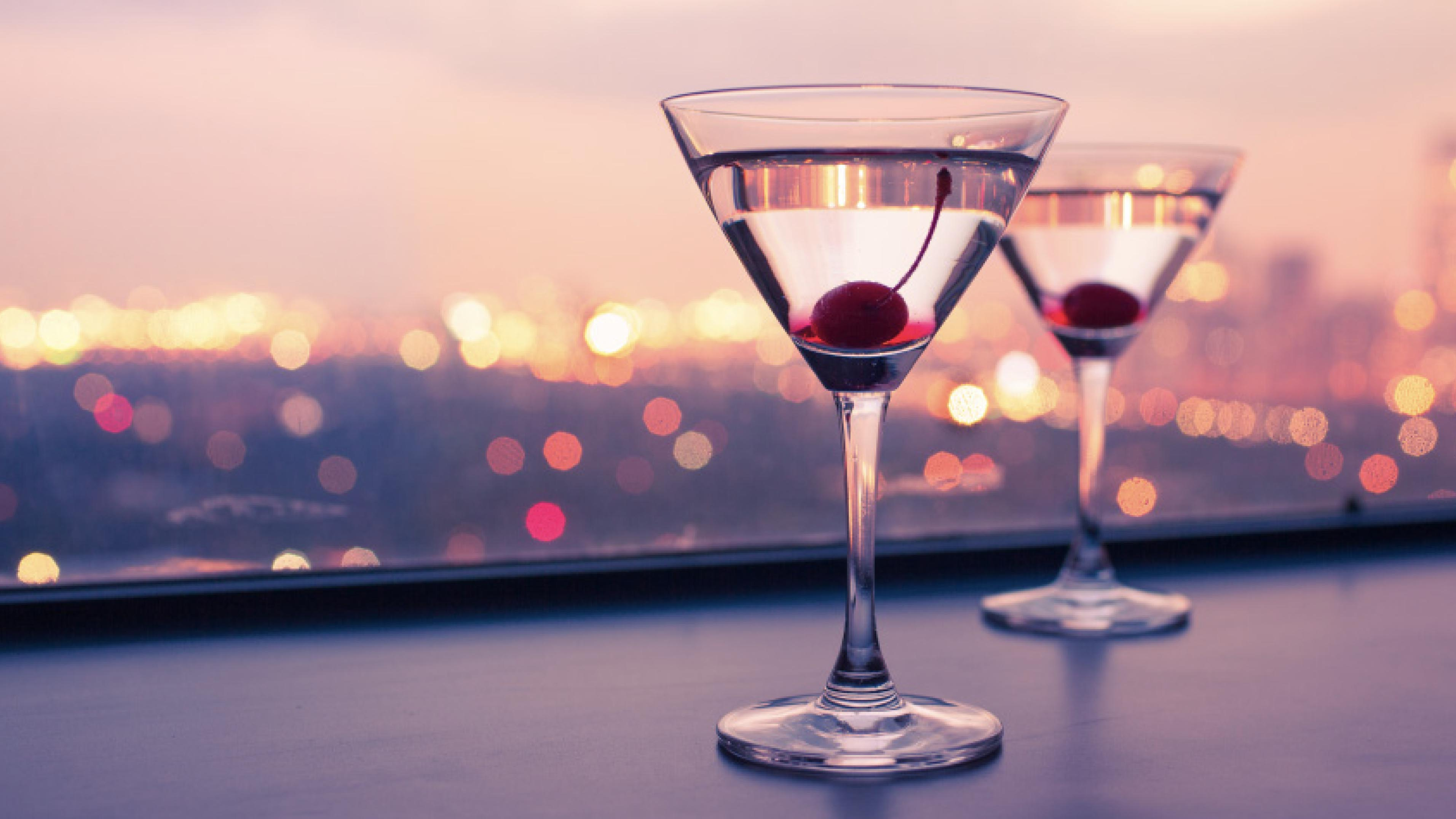 Two Drinks on a Rooftop Edge, in front of Blurred City Lights